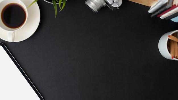 Draufsicht des trendigen arbeitsbereichs mit leerem bildschirmtablett, kaffeetasse, büromaterial und kopierraum