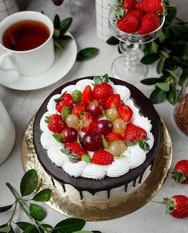 Draufsicht des tropfenden schokoladenkuchens, der mit erdbeere und trauben gekrönt wird