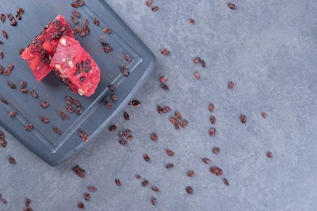Draufsicht des türkischen genusses lokum und der trockenen rosinen auf grauem holzbrett
