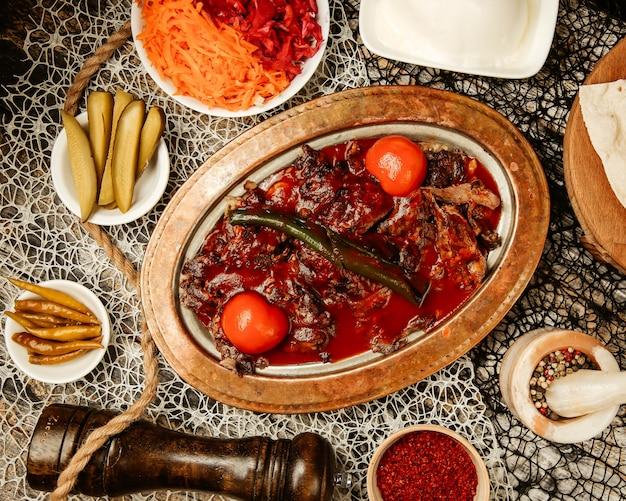 Draufsicht des türkischen iskender kebab serviert mit eingelegtem gurkenkohljoghurt rotem pfeffer