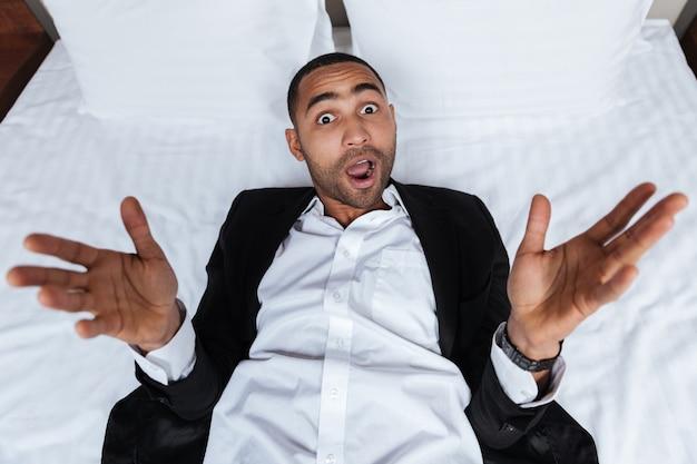 Draufsicht des überraschten afrikanischen mannes im anzug, der auf bett im hotelzimmer liegt und überraschte geste zeigt