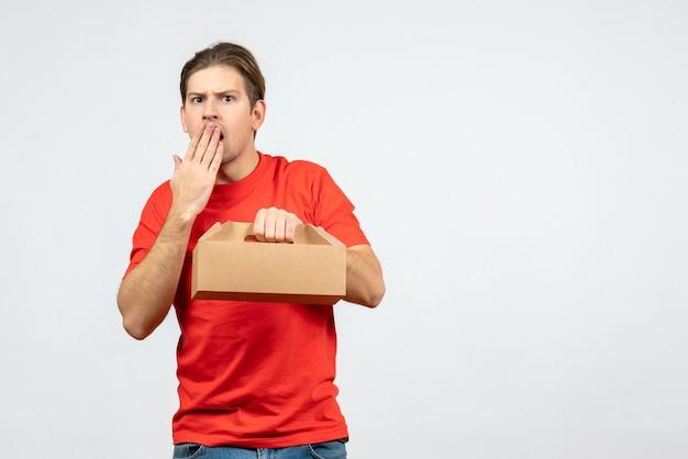 Draufsicht des überraschten und emotionalen jungen mannes in der roten bluse, die box auf weißer wand hält