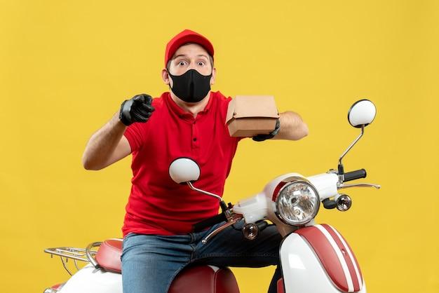 Draufsicht des überraschten zustellers, der rote bluse und huthandschuhe in der medizinischen maske trägt, die auf roller sitzt, der befehl zeigt, der vorwärts zeigt