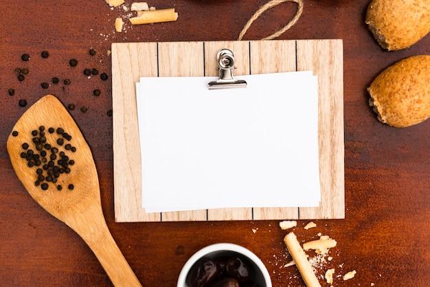 Draufsicht des unbelegten weißbuches mit klemmbrett; brötchen; brotstangen; pfefferkorn mit spachtel auf schreibtisch aus holz