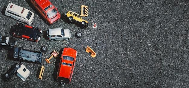 Draufsicht des unfalls der autos (miniatur, spielzeugmodell) auf straße. versicherungskonzept.