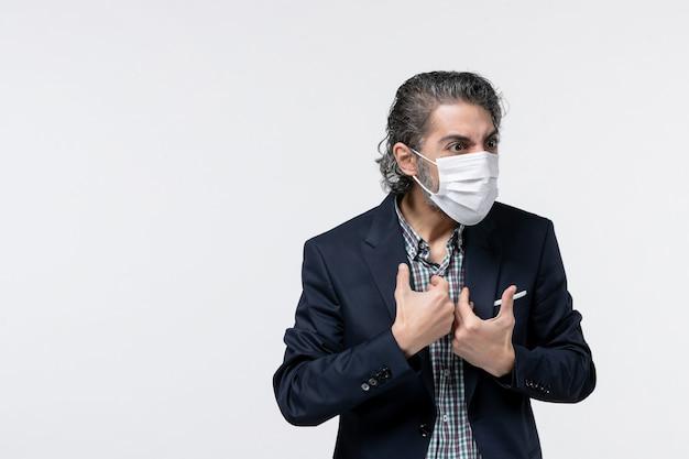 Draufsicht des unsicheren emotionalen jungen geschäftsmannes im anzug, der seine chirurgische maske auf weißem hintergrund trägt