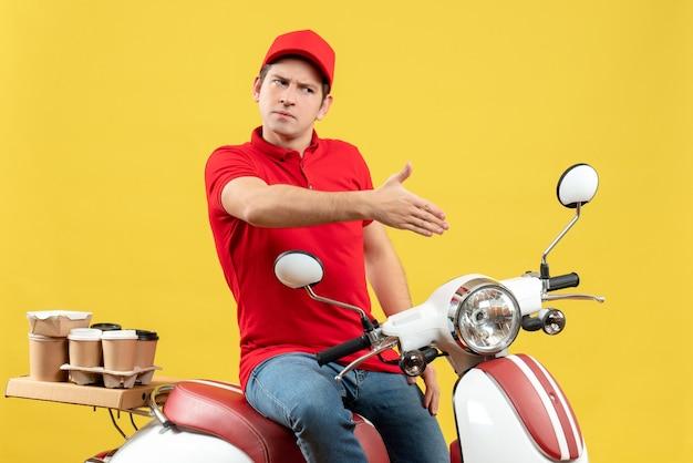 Draufsicht des unzufriedenen jungen kerls, der rote bluse und hut trägt und befehle liefert, die jemanden auf gelber wand begrüßen