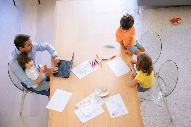 Draufsicht des vaters und der kinder, die zusammen am tisch sitzen. bruder und schwester malen kritzeleien mit bunten stiften. vater mittleren alters, der laptop benutzt und kleinen sohn hält. kindheits-, wochenend- und familienkonzept