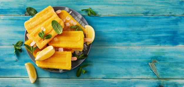 Draufsicht des veganen gelben eissorbetes auf blauem rustikalem hintergrund