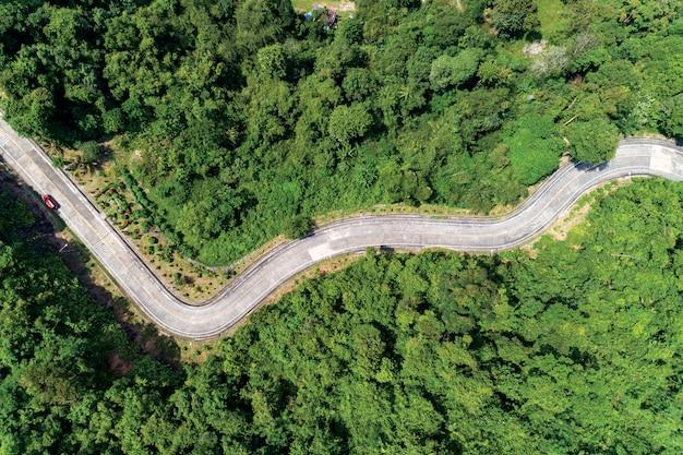 Draufsicht des vogelperspektivebrummenschusses der asphaltstraßekurve auf gebirgstropischem regenwald mit bergspitzen