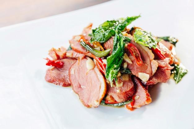 Draufsicht des wagyu-rindfleisches der nahaufnahme angebraten mit basilikum, knoblauch und paprika. japanische zutaten in thailändischem essen. asiatische fusionsküche.
