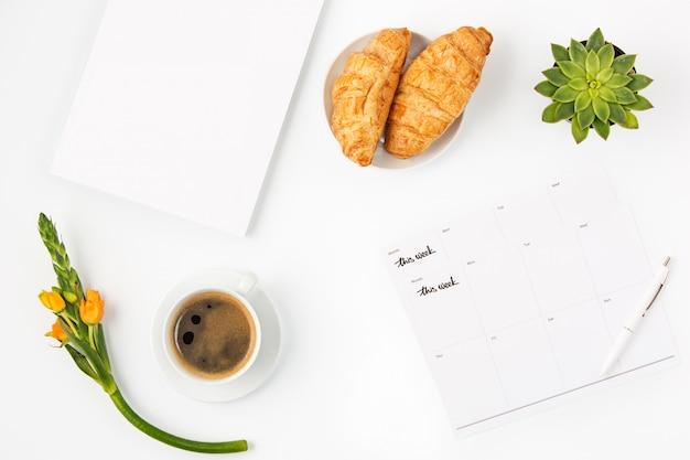 Draufsicht des weiblichen arbeitsbereichs des weißen büros mit notizbuch