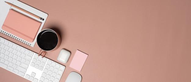 Draufsicht des weiblichen arbeitsbereichs mit computertastatur, tagebuchbuch, becher, zubehör und kopienraum auf rosa tisch
