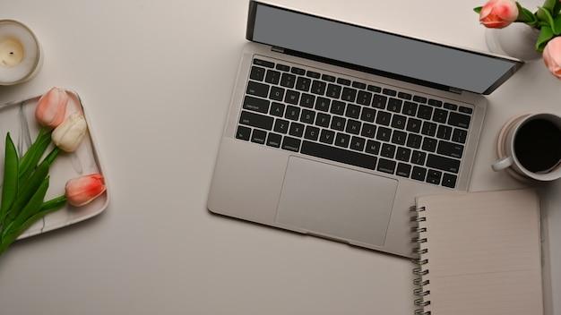 Draufsicht des weiblichen arbeitsbereichs mit laptop, notizbuch und blume verziert auf dem tisch