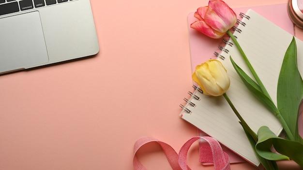 Draufsicht des weiblichen arbeitsbereichs mit laptop, notizbuch und blumen verziert auf dem rosa tisch