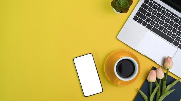 Draufsicht des weiblichen arbeitsplatzes mit computerlaptop, kaffeetasse, blumen, smartphone und kopienraum auf gelbem hintergrund.