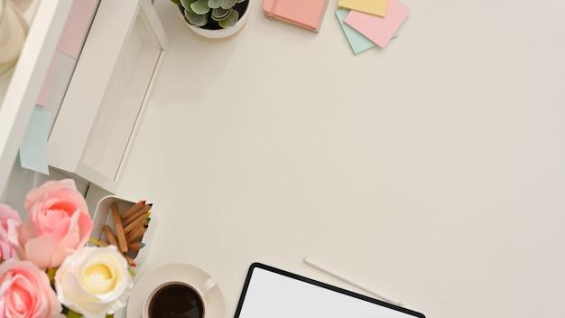 Draufsicht des weiblichen arbeitstisches mit kopienraum, tablette, kaffeetasse, briefpapier und blumenvase