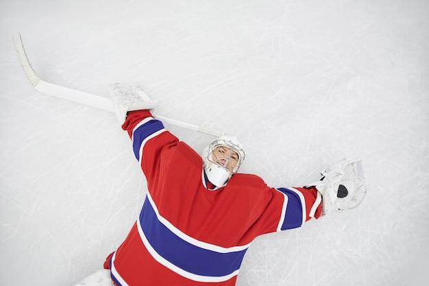 Draufsicht des weiblichen eishockeyspielers, der auf eis liegt und kamera betrachtet, die nach dem training erschöpft ist