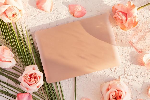 Draufsicht des weiblichen schreibtisches des büros mit laptop, tropischem blatt, rosa rosen blüht auf weiß mit schatten und sonnenlicht