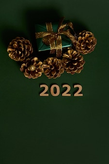 Draufsicht des weihnachtsgeschenks in glitzerpapier mit goldenem bogen und goldfarbenen tannenzapfen, ziffern aus holz als symbol für das jahr 2022 auf dunkelgrünem hintergrund mit kopierraum
