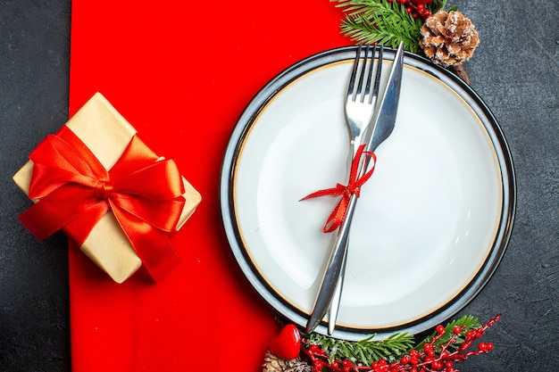 Draufsicht des weihnachtshintergrundes mit besteck, das mit rotem band auf einem teller mit dekorationszubehör für tannenzweige neben einem geschenk auf einer roten serviette gesetzt wird