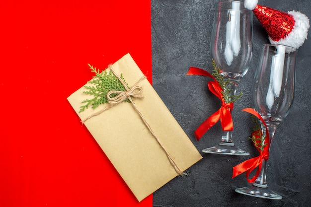 Draufsicht des weihnachtshintergrundes mit den glasbechern des weihnachtsmannhutes und des geschenks auf rotem und schwarzem hintergrund