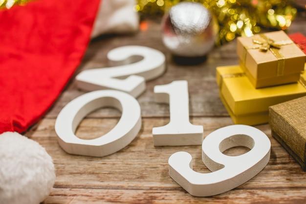 Draufsicht des weihnachtshutes, der zahl 2019 und der geschenkboxen auf hölzernem hintergrund.