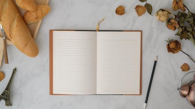 Draufsicht des weinlese-herbstarbeitsbereichs mit offenem notizbuch, brot und dekorationen auf marmortisch