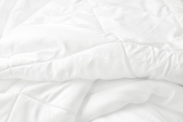 Draufsicht des weißen bettwäscheblatts und der unordentlichen decke der falte im schlafzimmer nach aufwachen.