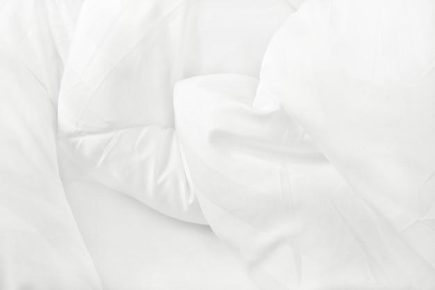 Draufsicht des weißen bettwäschebogens und der unordentlichen decke der falte im schlafzimmer nach wachen auf.