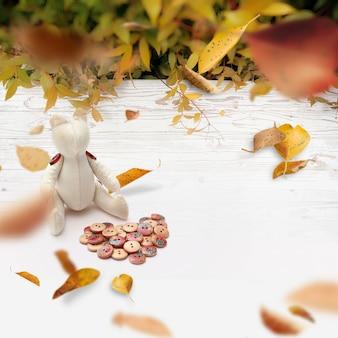 Draufsicht des weißen holzfußbodens im garten mit handgemachtem bären und herbstlaub valentinstagkonzepthintergrund