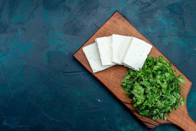 Draufsicht des weißen käses mit frischem grün auf dunkelblauer oberfläche