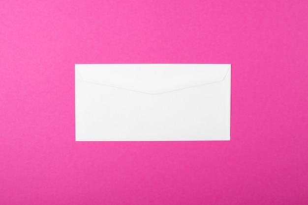 Draufsicht des weißen leeren umschlags auf rosa hintergrund.