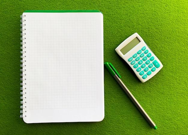 Draufsicht des weißen notizbuches über grüne tabelle