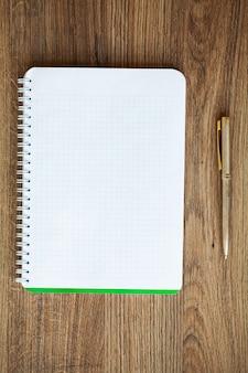 Draufsicht des weißen notizbuches über holztisch.
