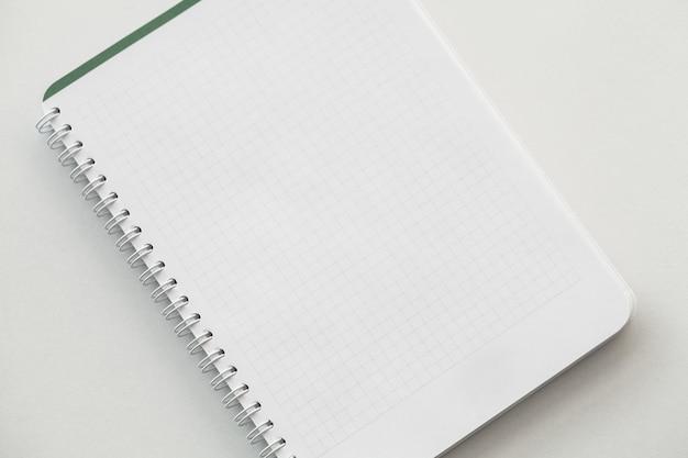 Draufsicht des weißen notizbuches über weiße tabelle