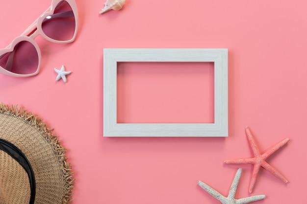 Draufsicht des weißen rahmens, der sonnenbrille, des strohhutes auf rosa c