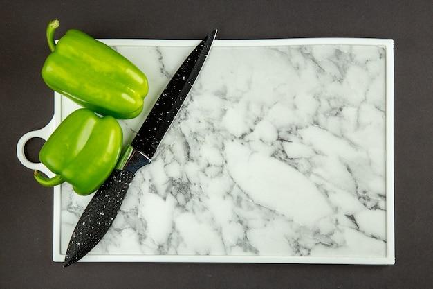 Draufsicht des weißen schneidebretts mit grünem paprika auf dunkler oberfläche