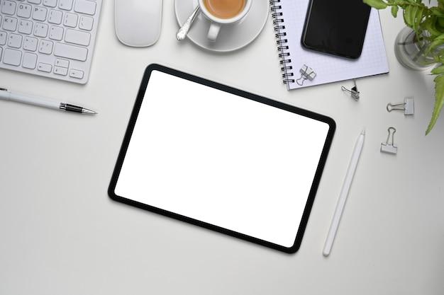 Draufsicht des weißen schreibtischs mit digitalem tablet, smartphone und büromaterial.