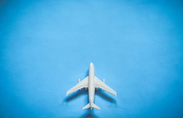 Draufsicht des weißen spielzeugflugzeugmodells über blauem farbhintergrund