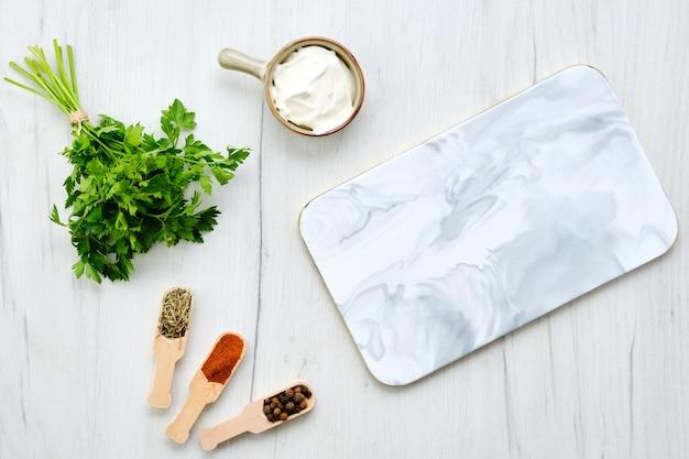 Draufsicht des weißen tisches mit marmor-servierteller und gewürz