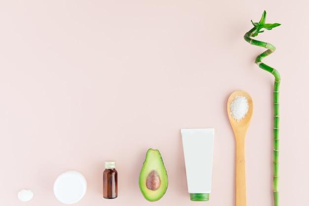 Draufsicht des weißen und grünen kosmetiksatzes und -bambusses für gesichtshautpflege und badekur auf rosa, flacher lage, platz für text.
