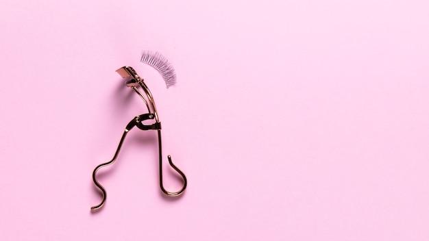 Draufsicht des wimperlockenwicklers auf rosa hintergrund
