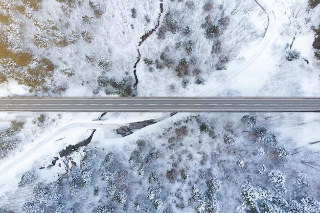Draufsicht des winterwaldes und der straße