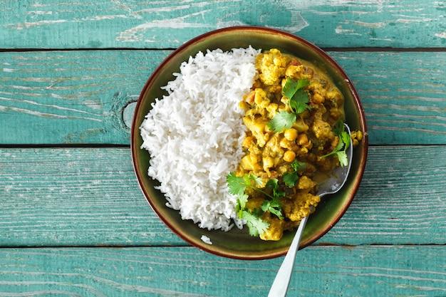 Draufsicht des würzigen curryreises des blumenkohls hölzernen copyspace