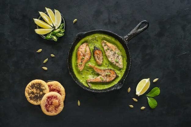 Draufsicht des würzigen und heißen bengalifischcurrys. indisches essen. fischcurry mit grünem paprika, curryblatt, kokosmilch. asiatische küche.