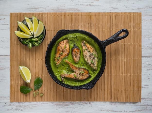Draufsicht des würzigen und heißen bengalischen fischcurrys. indisches essen. fischcurry mit grünem chili, curryblatt, kokosmilch. asiatische küche.