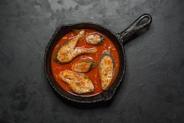 Draufsicht des würzigen und heißen bengalischen fischcurrys. indisches essen. fischcurry mit rotem chili, curryblatt, kokosmilch. asiatische küche.