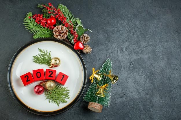 Draufsicht des zahlendekorationszubehörs auf einem plattentannenzweig-nadelbaumkegel neben weihnachtsbaum auf dunklem hintergrund