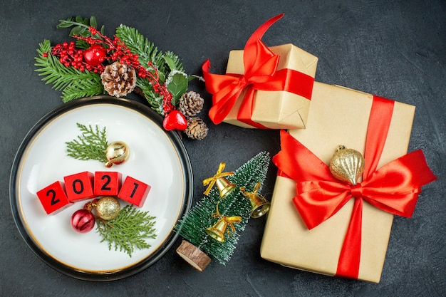Draufsicht des zahlendekorationszubehörs auf einer platte tannenzweige nadelbaumkegel und geschenkboxen mit bogenförmigem rotem band auf dunklem hintergrund